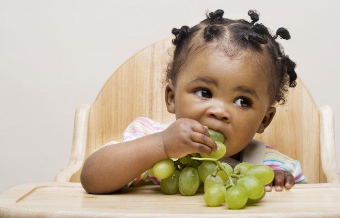 Baby girl eating grapes