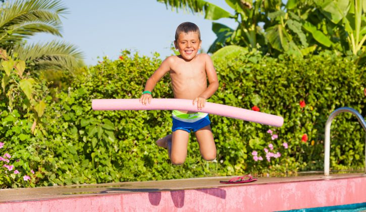 Jumping small boy holding inflatable ring standing near the swimming pool outside in summer
