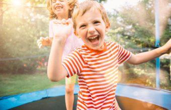 Children having fun on summer vacation jumping on trampoline
