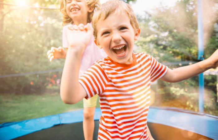 Children having fun on summer vacation jumping on trampoline