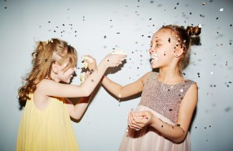 Two girls having fun with birthday cake cream at party