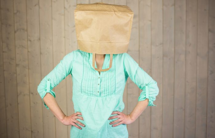 Woman covering head with brown paper bag while standing against wall