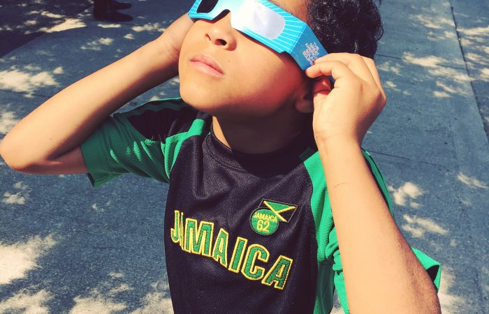 child looking at eclipse through glasses