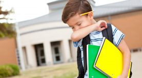 Young boy at school coughing into his arm.