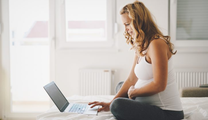 Pregnant expectant and happy  woman using technology from home