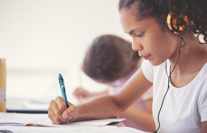 Young Aboriginal girls studying with headphones. They are working at a table at home. One girls listening to music or educational work as she works. They are sisters doing schoolwork together.