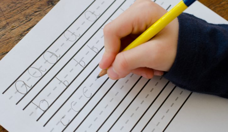 Child practising writing their letters abc