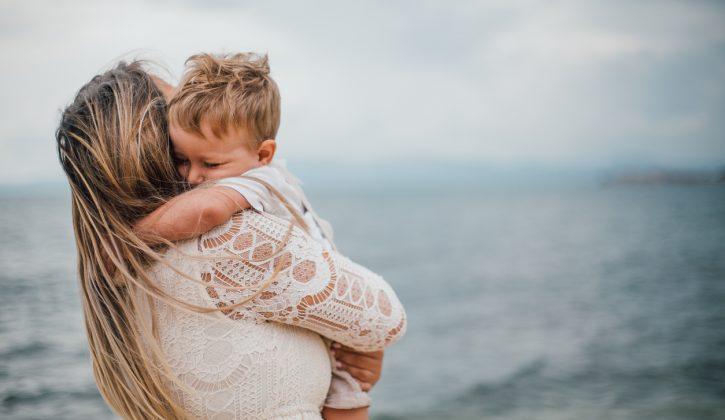 Alleinerziehende Mutter spielt am Strand mit ihrem Sohn