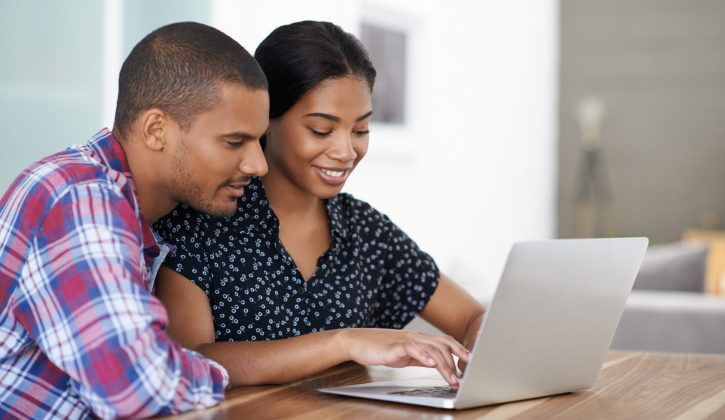 Shot of a young couple sitting at their dining table using a laptop