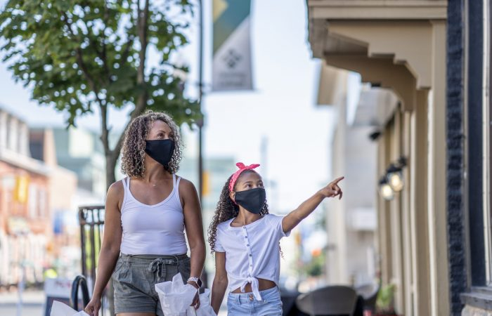 African American mother and daughter shopping downtown while wearing masks