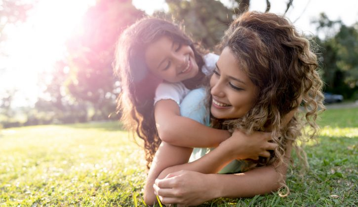 Beautiful portrait of a Latin American mother playing with her daughter outdoors and hugging - family concepts
