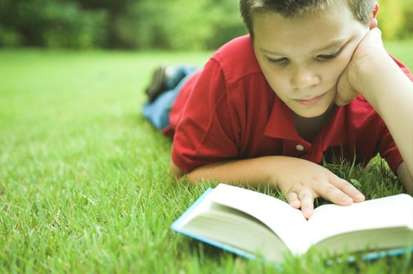 boy-reading-book-outside