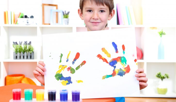 Cute little boy with his colorful handprint